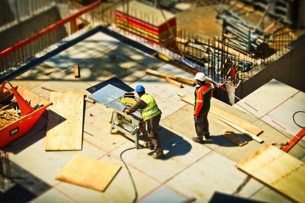 Architekten und Bauarbeiter arbeiten Hand in Hand